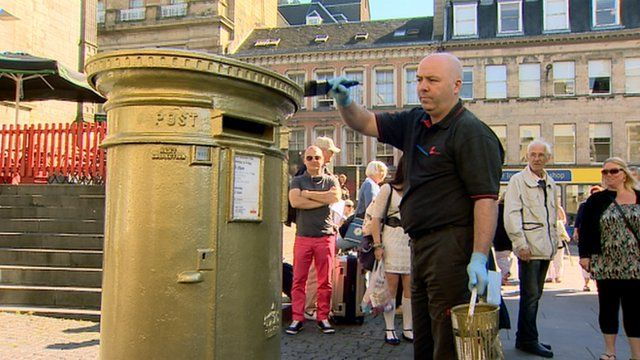 A man paints a post box gold for Sir Chris Hoy's second Olympic gold medal win