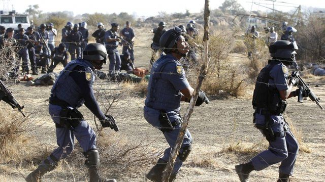 Policemen react after firing shots at protesting miners outside a South African mine in Rustenburg