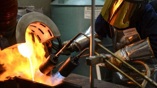 A goldsmith controlling the fire during the melting of gold to produce a gold ingot