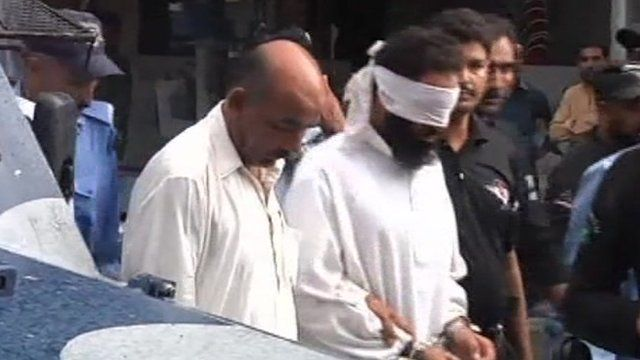 Imam in blindfold and handcuffs