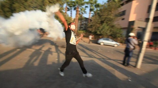 Protester in Cairo throwing a cannister of tear gas