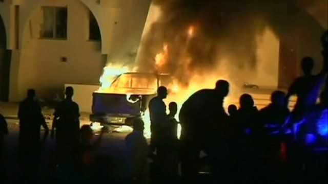 Protesters watch as a car burns in Benghazi