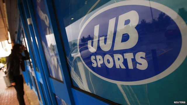 Woman looks in a closed JJB Sports store