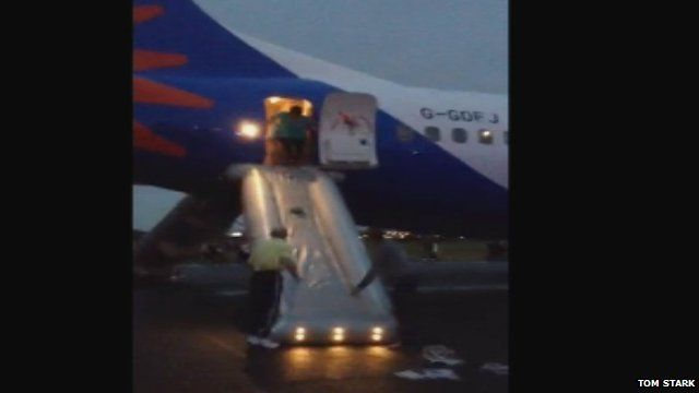 Passengers evacuate a plane using chutes