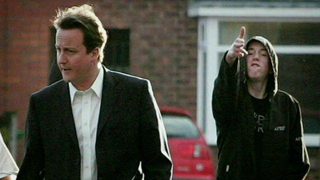 Hoodie standing behind David Cameron