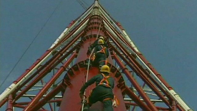 Workers climb the huge pylon in Anhui Province
