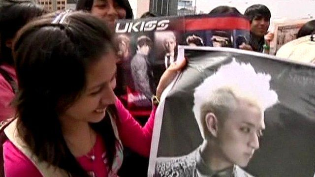 A fan holds up a poster