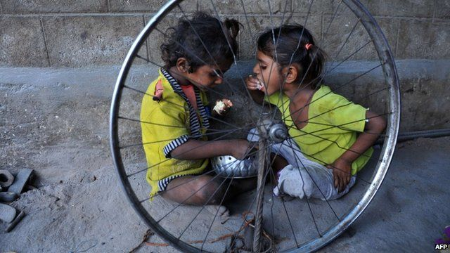 Indian children eat food at their temporary shelter on the side of a road in Hyderabad