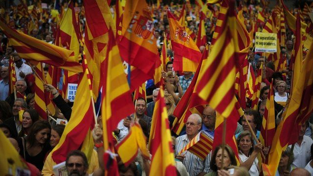 People opposed to the independence of Catalonia hold Catalan and Spanish flags during the holiday known as Dia de la Hispanidad