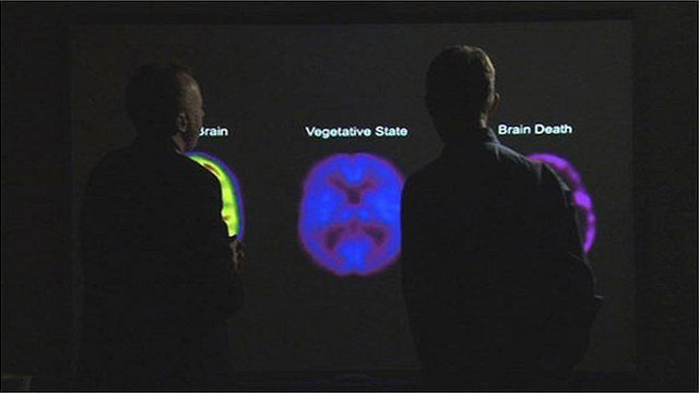 Prof Owen in front of PET brain scans