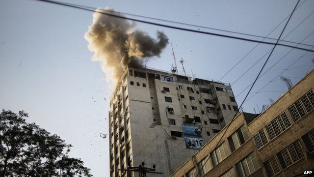 Smoke billows as debris flies from the explosion at the local Al-Aqsa TV station in Gaza City on November 18, 2012