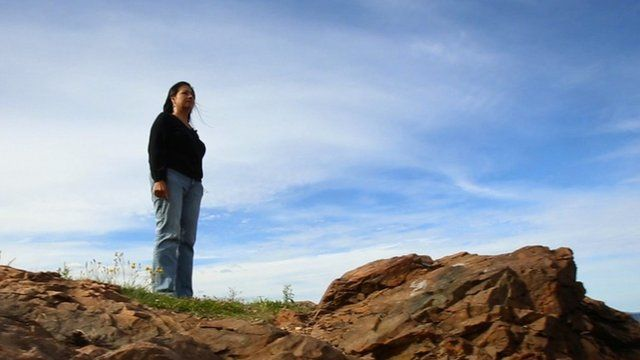 Woman on rock staring out to sea
