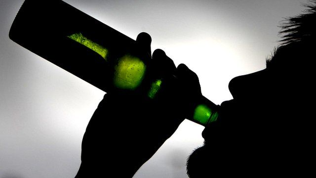 Silhouette of man drinking from bottle