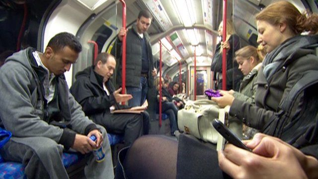 Rory Cellan-Jones reads his paper while other Tube commuters check their smartphones