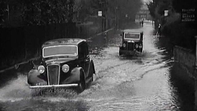 Vintage cars drive through floods