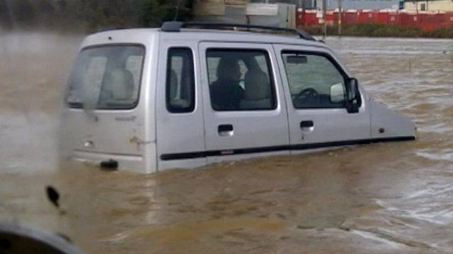 Car driver trapped in flood water