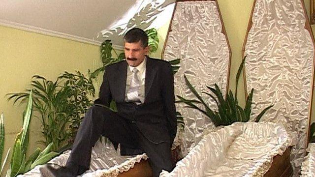 Man climbing into coffin