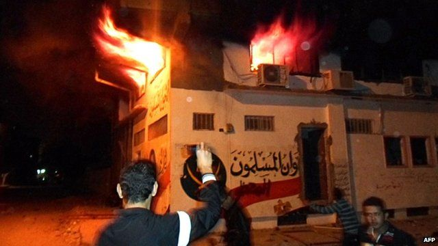 Egyptian protesters stand outside the burning office of the Muslim brotherhood in Ismailia