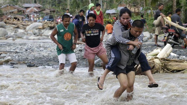 Residents cross a river in the flood-hit village of Andap