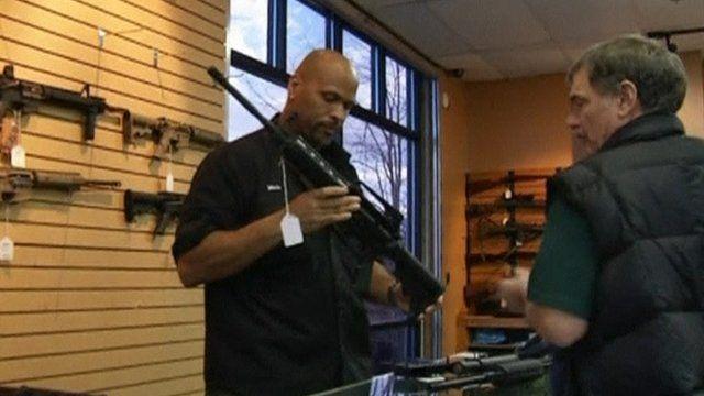 Gun store salesman showing customer an AR 15-style rifle