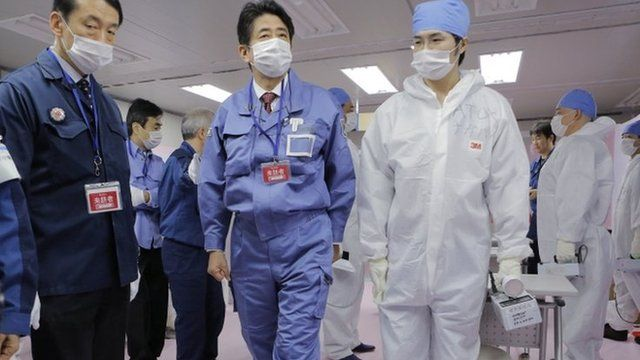 Japan's Prime Minister Shizo Abe with workers at the Fukushima Dai-ichi nuclear power plant (29 Dec 2012)