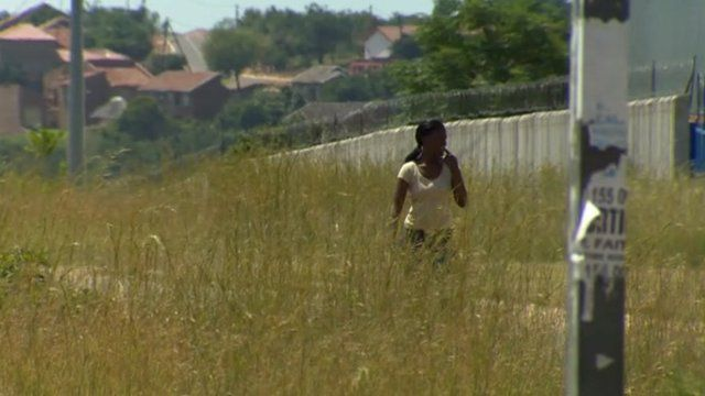Woman walks down South Africa street lined by tall grass