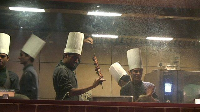Men preparing a meat dish in a restaurant in Mumbai