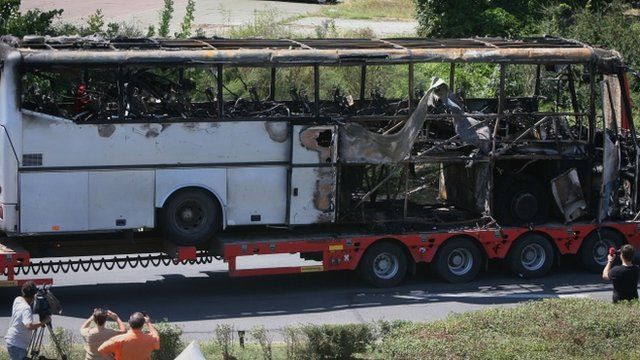 A damaged bus is being transported out of Burgas airport, Bulgaria