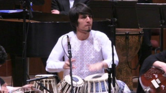 Member of orchestra playing drums