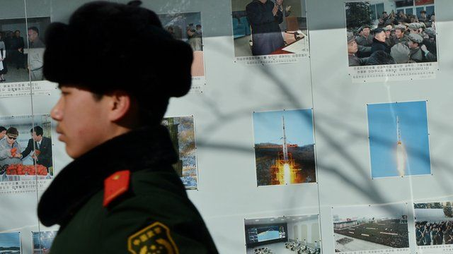 A Chinese policeman marches past photos of North Korea's recent rocket launch outside the North Korean embassy in Beijing