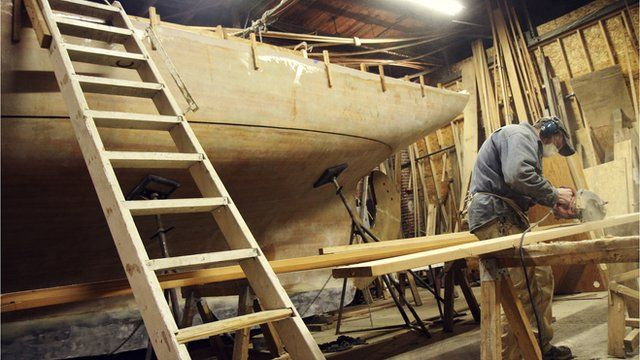 Jonah Eaton works on his wooden yacht