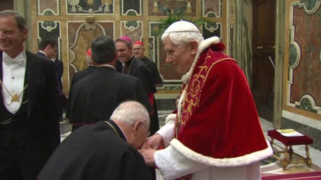 A cardinal kisses Pope Benedict's hands