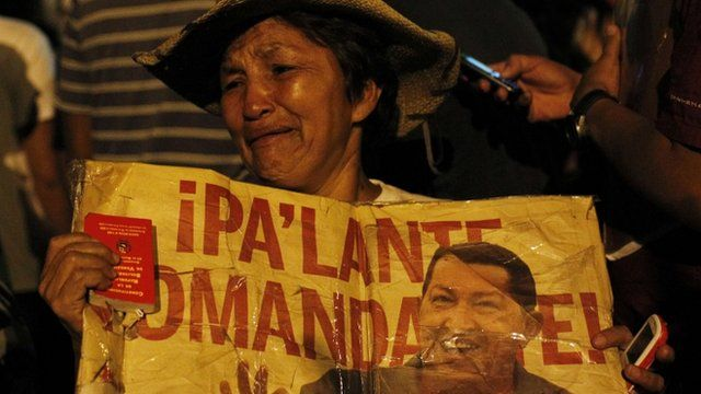 Woman cries holding poster of Hugo Chavez