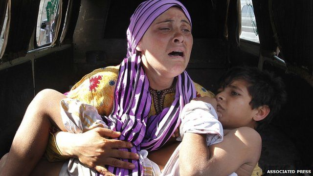 A Syrian woman carries her wounded son