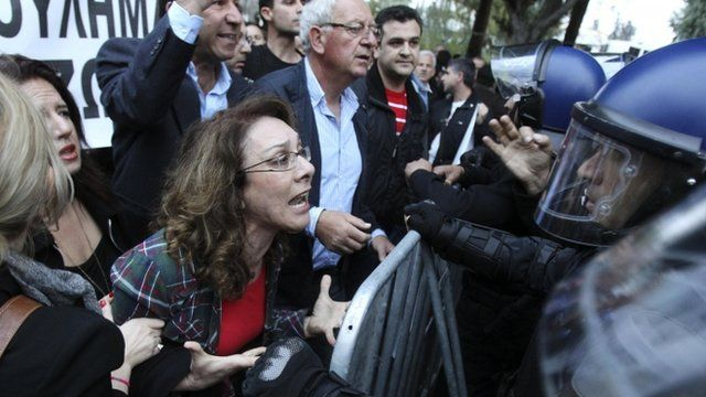 A woman shouts at policemen during a protest outside the parliament in Nicosia