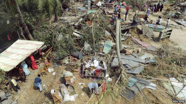 People retrieve their belongings from the wreckage after a tornado hit Bangladesh