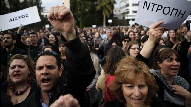 "Employees of the Bank of Cyprus shout slogans as they holds banners reading in Greek ""shame"" during a protest at Cyprus central bank in Nicosia"