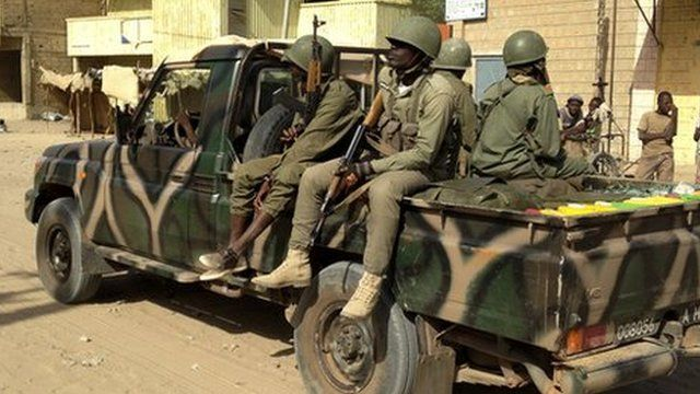 Malian soldiers patrol the streets