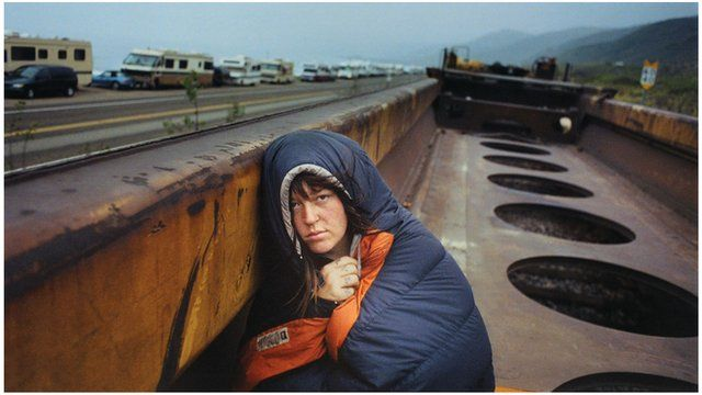A homeless person riding on a freight train