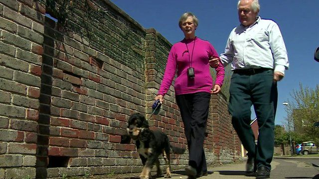 Husband walks with his wife who has dementia