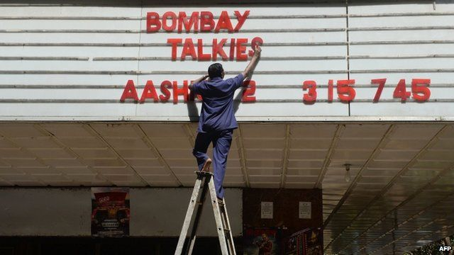 "An employee of the New Excelsior Theatre puts up letters spelling out the movie ""Bombay Talkies"" in Mumbai"