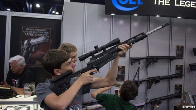 A teenager takes aim with a gun made by Colt at a booth during the National Rifle Association's annual meeting in Houston, Texas.