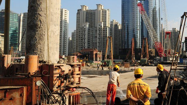 Labourers work at a new property development under construction on the busy Nanjing Road shopping street in Shanghai