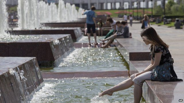 People sit at a fountain in a park in Moscow, Russia