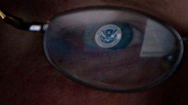 Logo of US Homeland Security office reflected in glasses