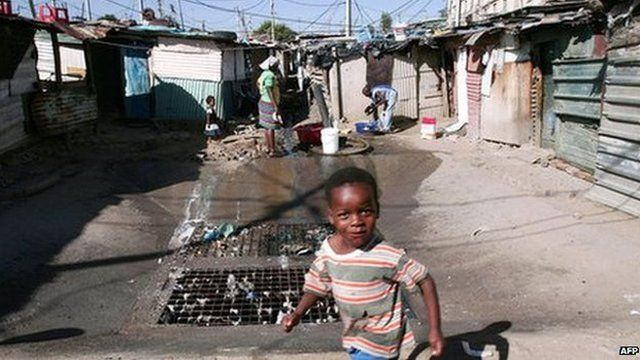 A child runs around in the washing area as her mother does her washing in Johannesburg Alexandra township (archive shot)