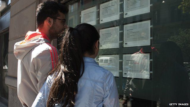Two people look at job announcements on the window of an agency in Naples