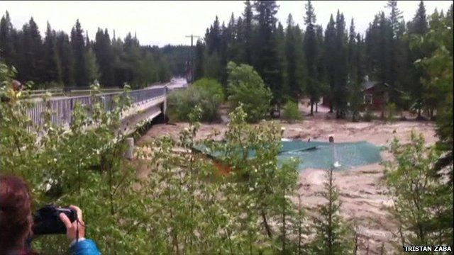 A still from amateur footage shows a roof floating on Bragg Creek, Alberta