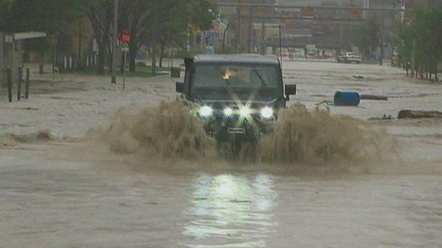 Four-wheel drive vehicle driving through flooded street