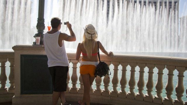 Tourists watch the Bellagio fountain show during a heat wave